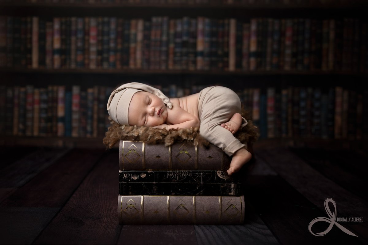 Little newborn boy lying on a stack of books