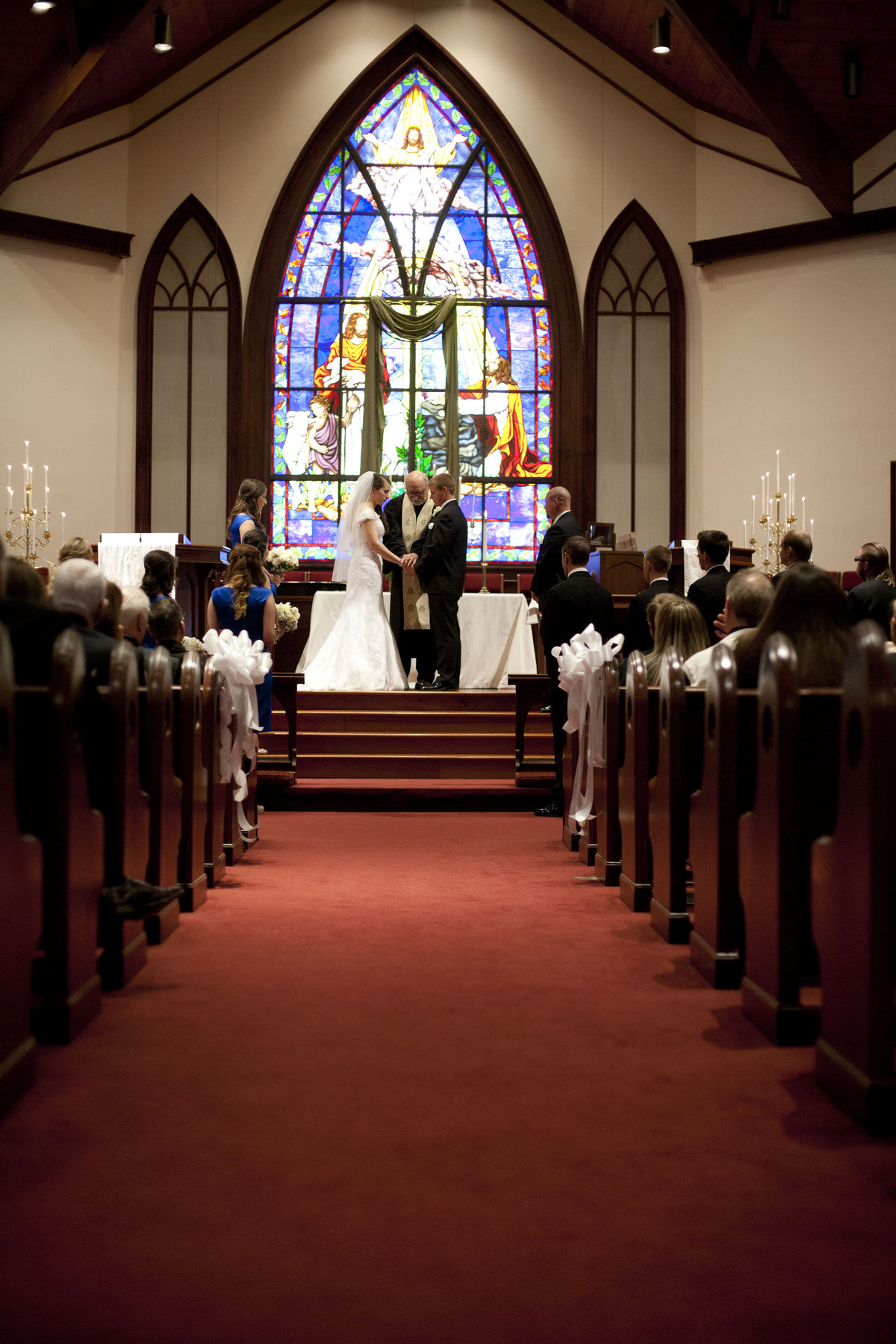 Wedding Ceremony in a church with stain glass window