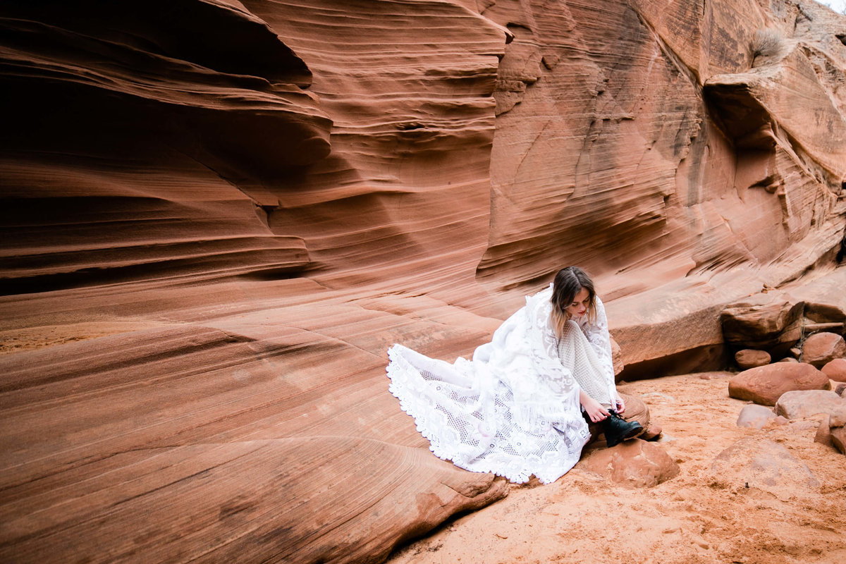 the boho bride sits in a slot canyon and laces her boots. her lace dress fans out beside her.