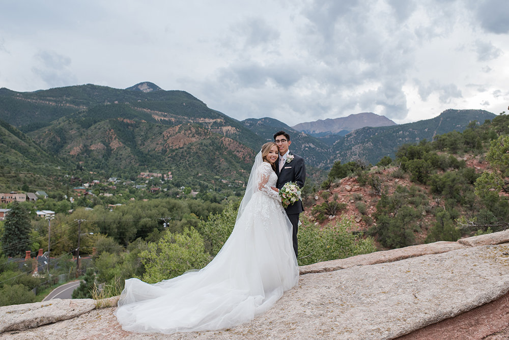 Bride and groom on red rocks with pikes peak