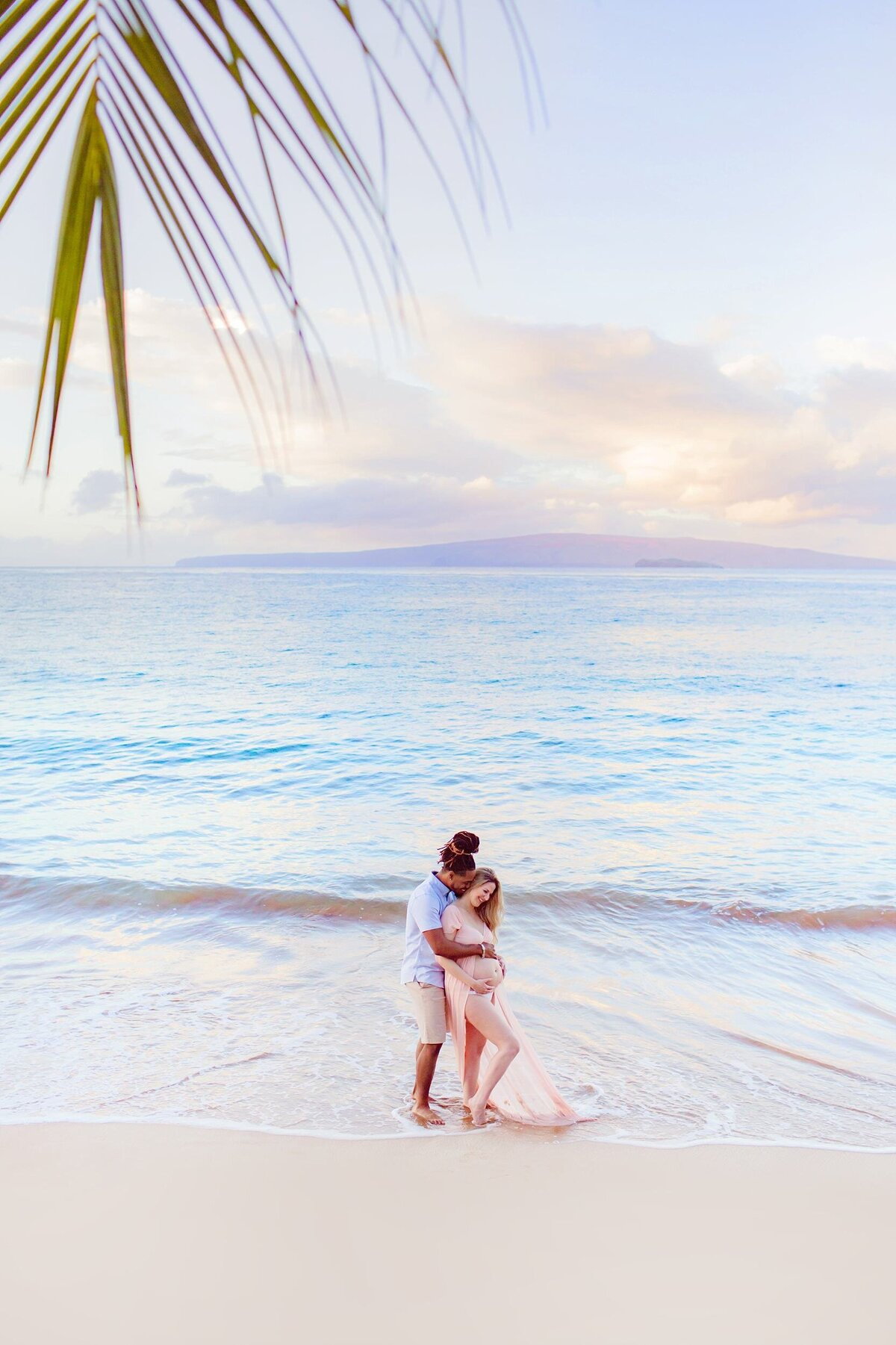 Vertical image of man kissing pregnant wife on Maui