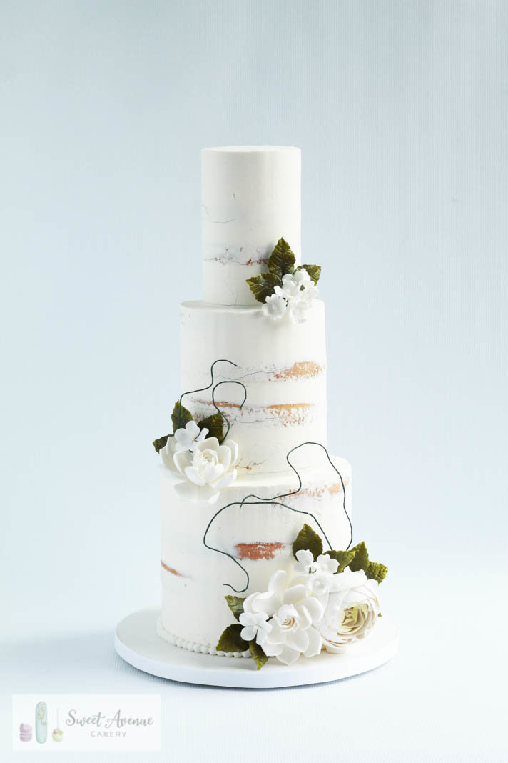 semi naked rustic buttercream wedding cake with flowers