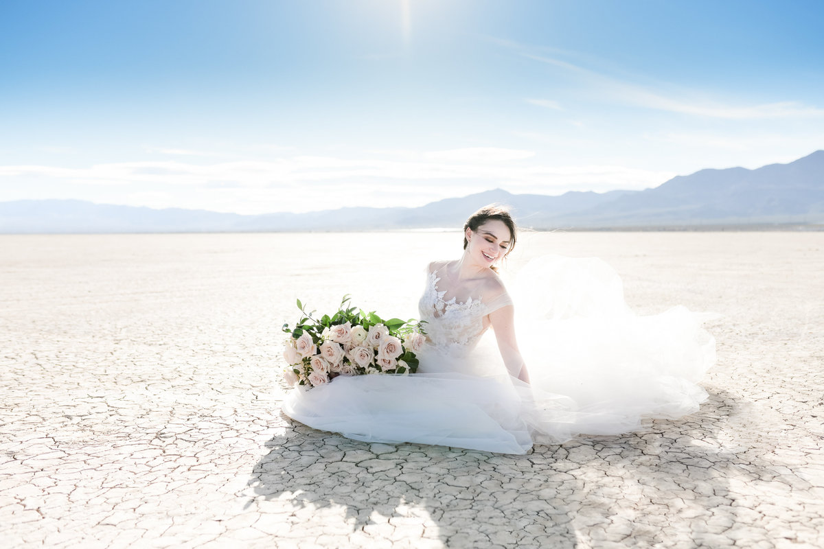 windswept bride holds bouquet while sitting in wedding gown in desert