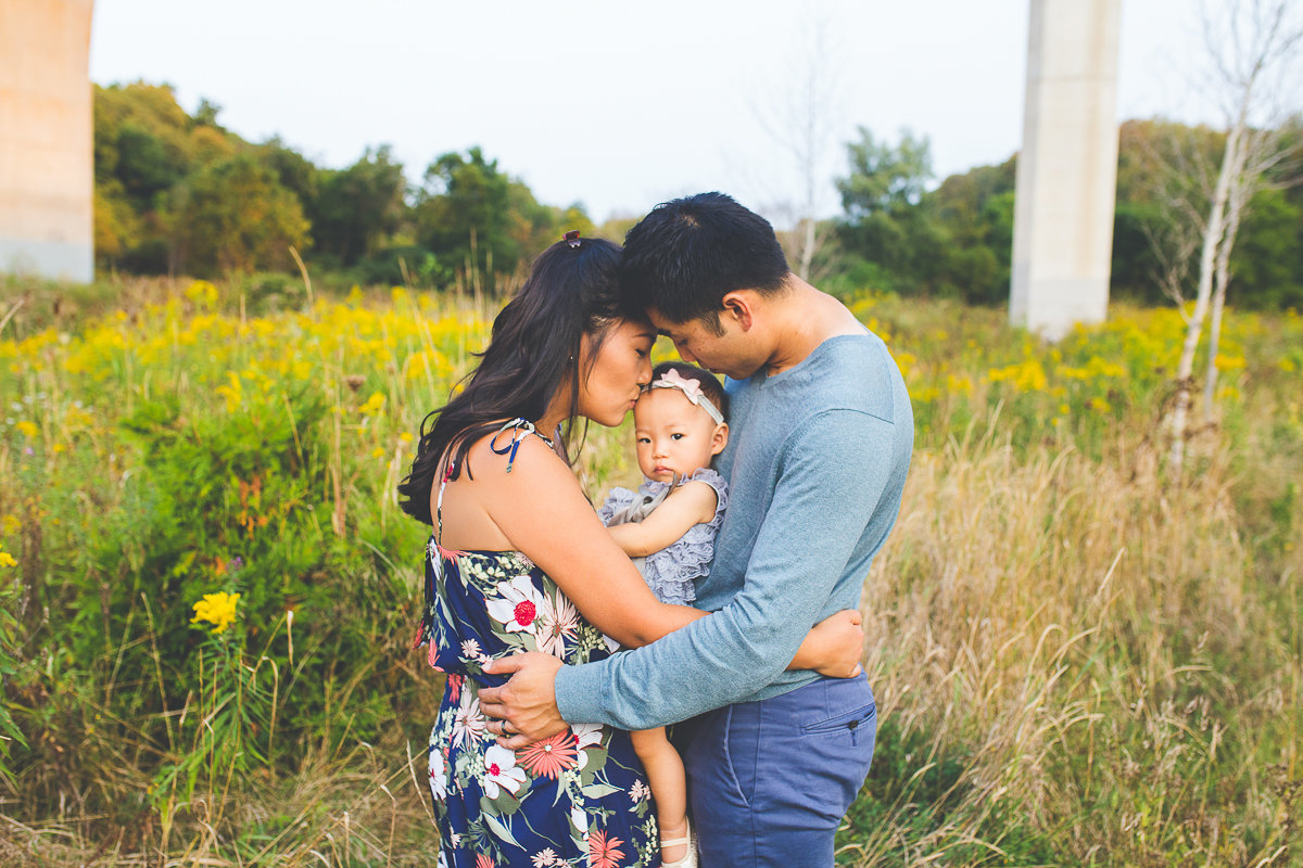 Parents hugging with baby girl between them outdoors {Oakville Family Photographer}