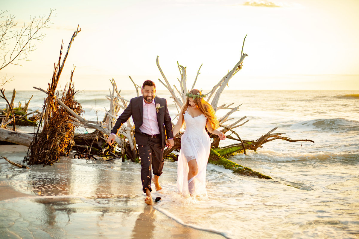 Groom smiles at camera as he holds hands with bride in her white wedding dress and floral crown as they run down the beach splashing in the ocean water at sunset in St. Petersburg, Florida
