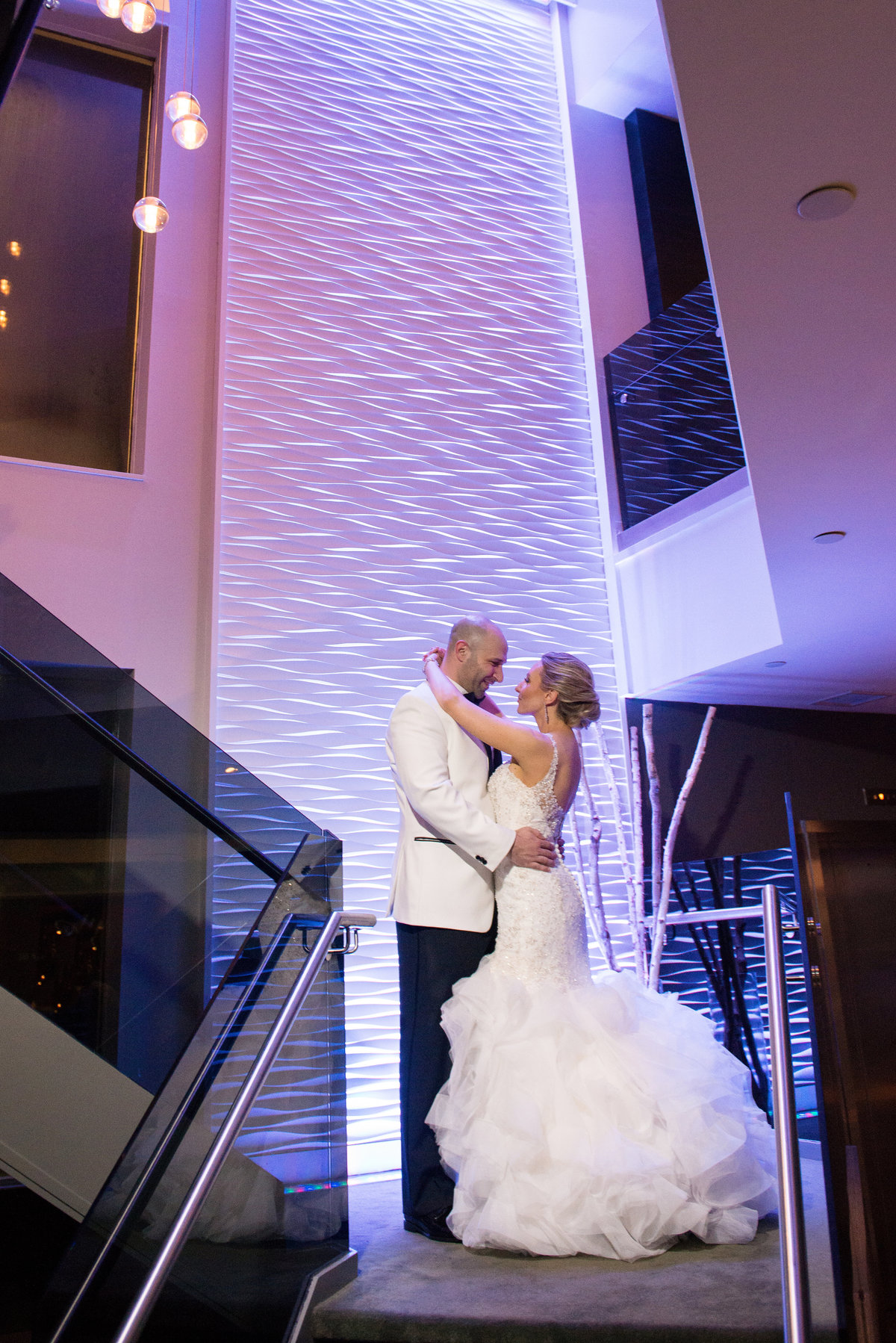 Bride and Groom at the stairs of Harbor Club at Prime with purple uplighting