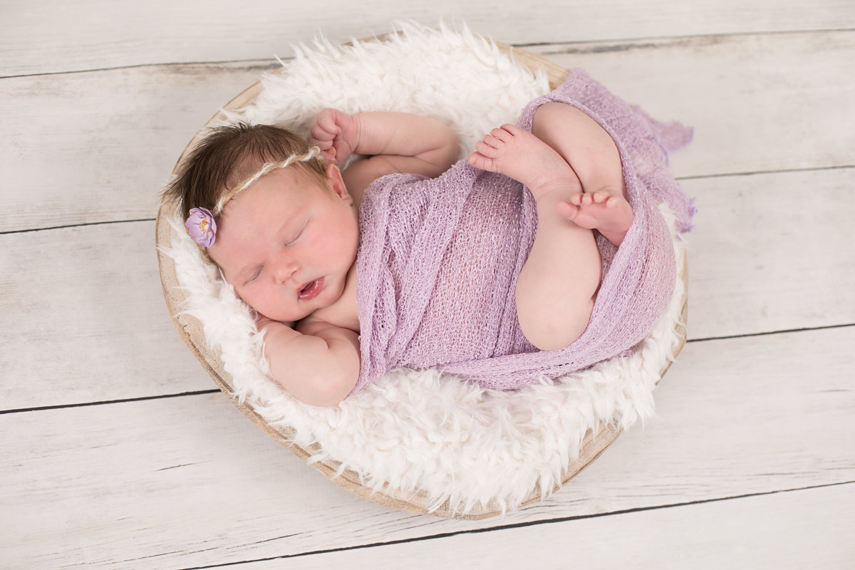 Newborn baby in lavender wrap with a flower headband lying in a basket on a white plank wood floor