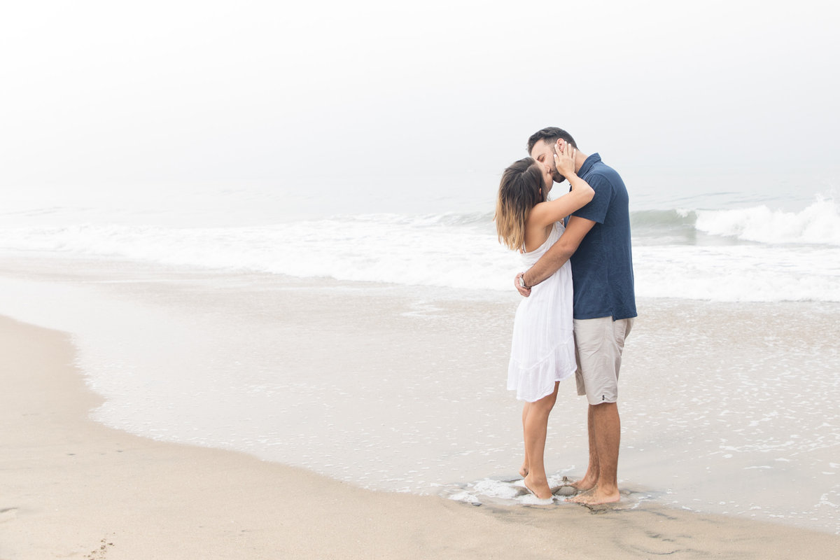 Husband and wife kissing on the beach as the waves touch their toes