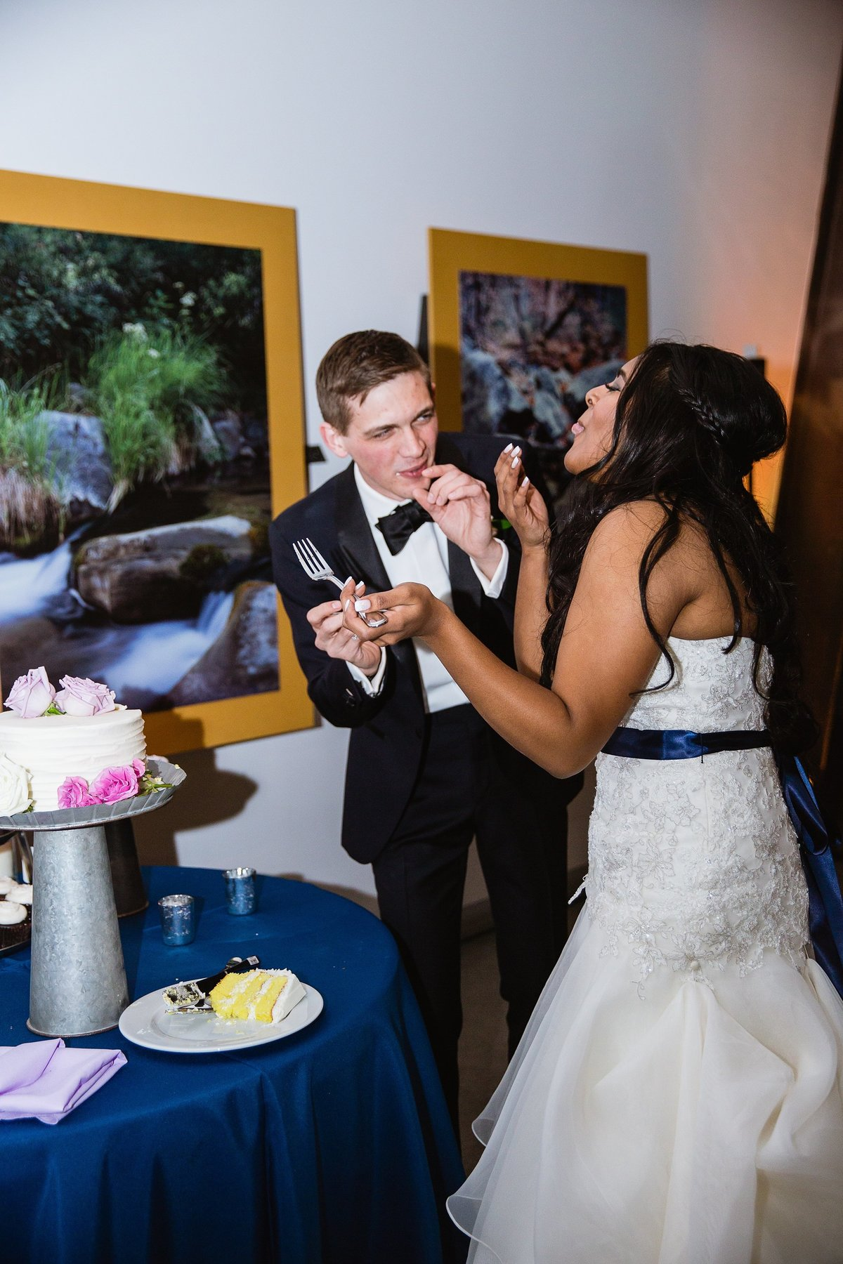 Bride and groom cutting the cake at their wedding reception by Phoenix wedding photographer PMA Photography.