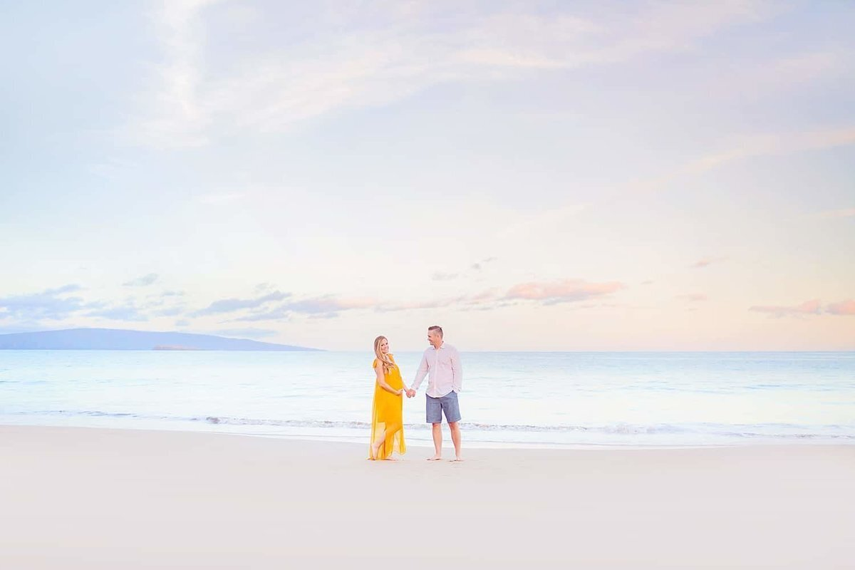 Woman in yellow maternity gown on Maui glances up at her husband on the beach