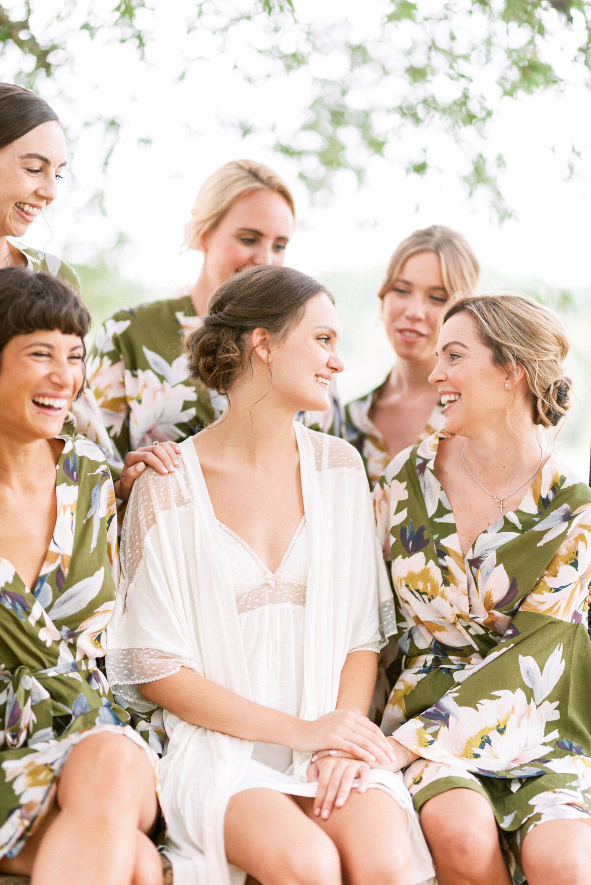 Bridesmaids in floral robes gather around their bride