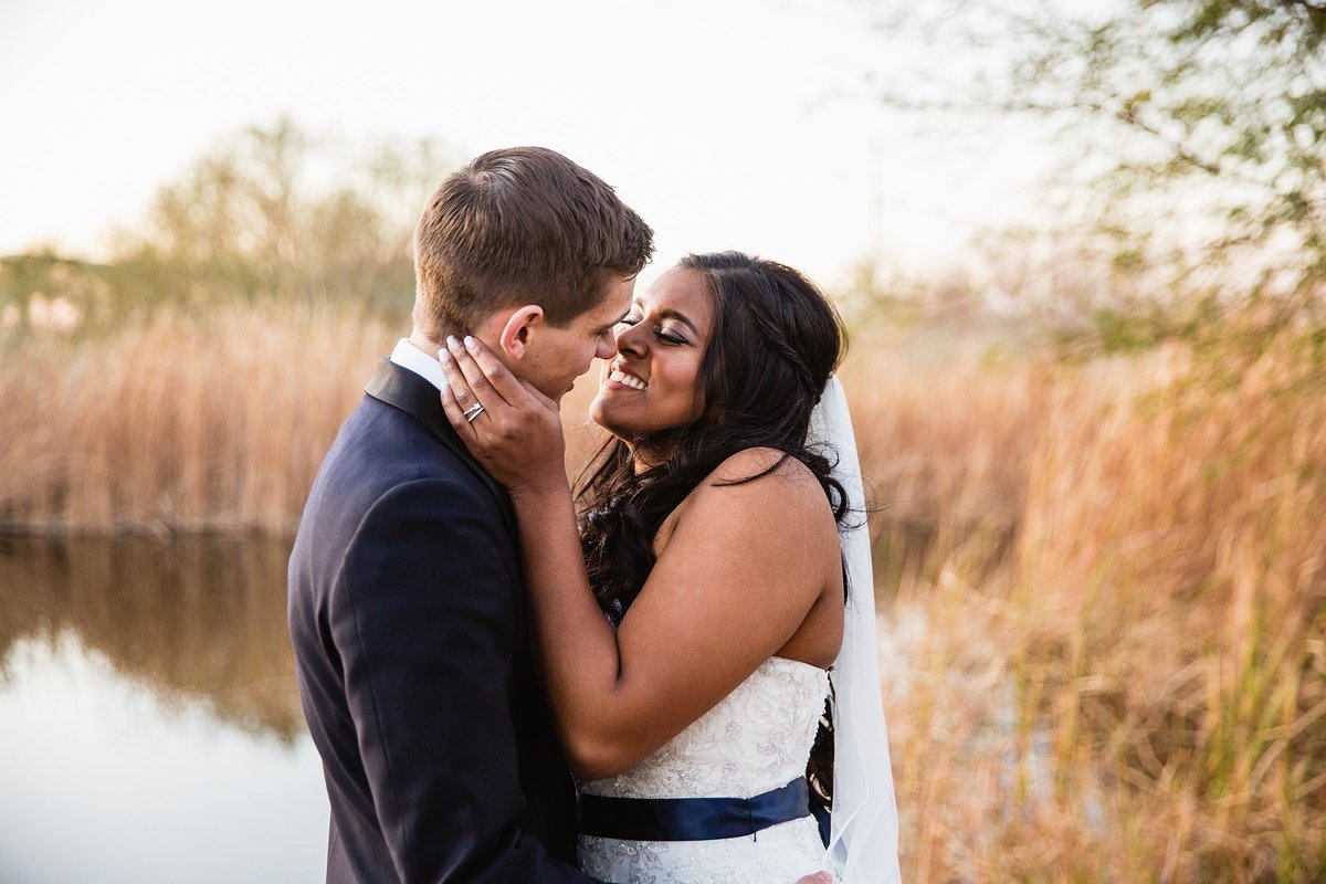 Bride and groom sharing a romantic moment at their desert wedding by Phoenix wedding photographer PMA Photography.