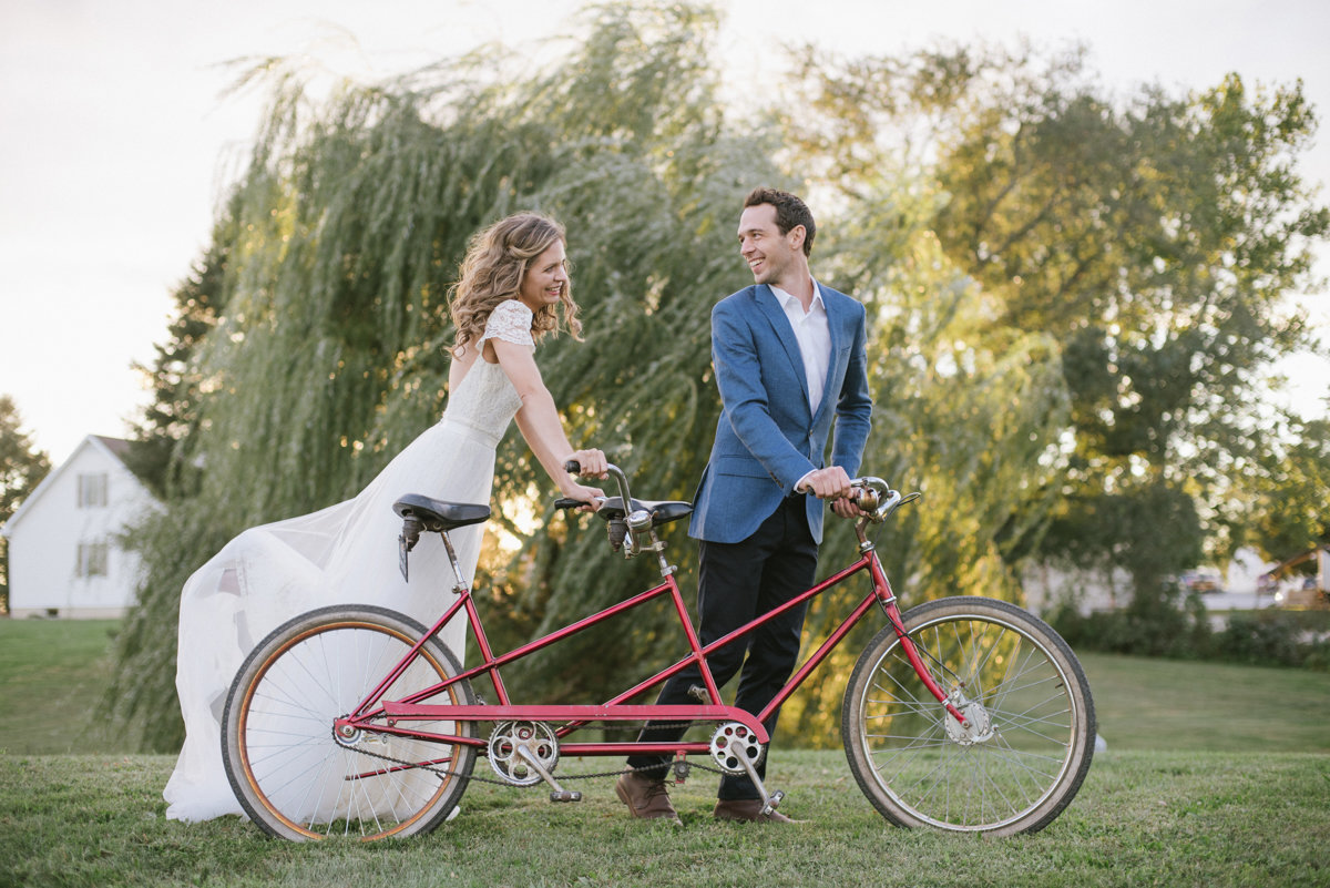Soft romantic whimsical wedding photo with a bicycle made for two