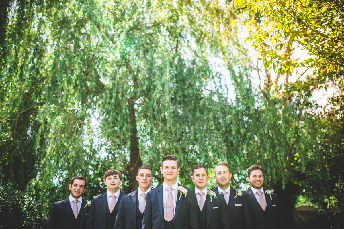 grooms men in formation posed in front of trees creatively