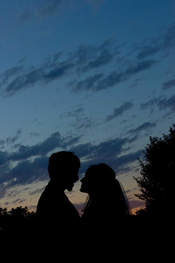 A silhouette shot of a bride and groom looking at each other with a sunset in the background