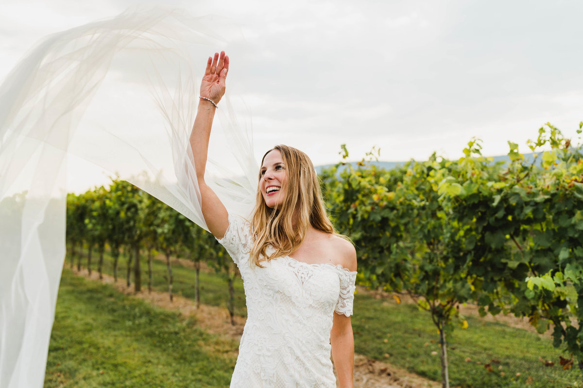 A photo of a bride at Kalero Vineyard tossing her veil in the wind