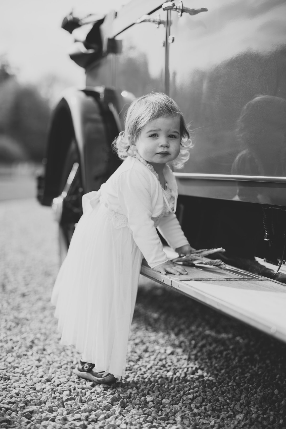 a flower girl leaning on the step of a vintage wedding car