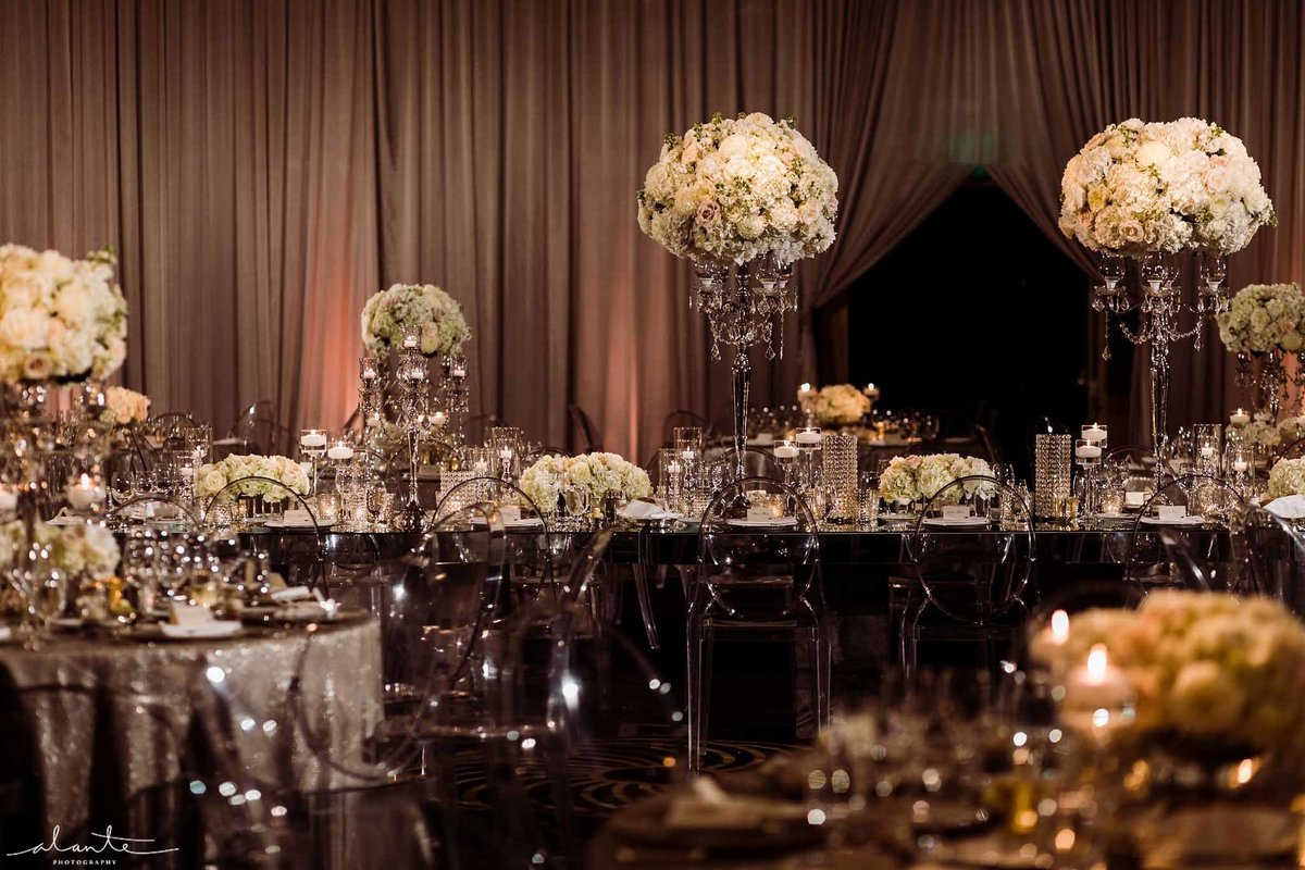Clear lucite ghost chairs and silver sparkle linens with white floral.