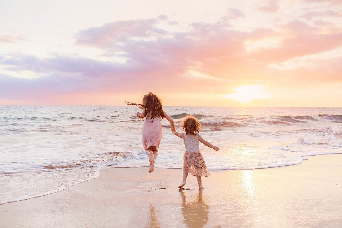 Sisters jump at sunset on Maui during beach family portrait session
