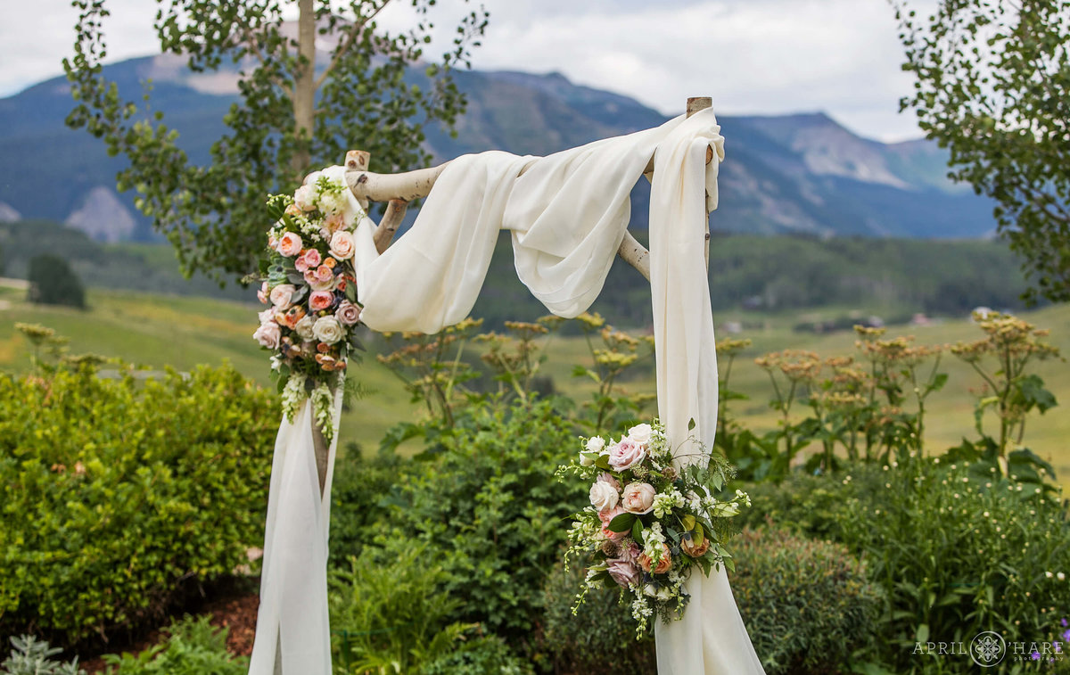 Lucky Penny Wedding Planner custom wood arch with floral design in Crested Butte Colorado