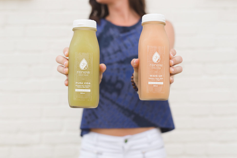 girl holding two cold press juices