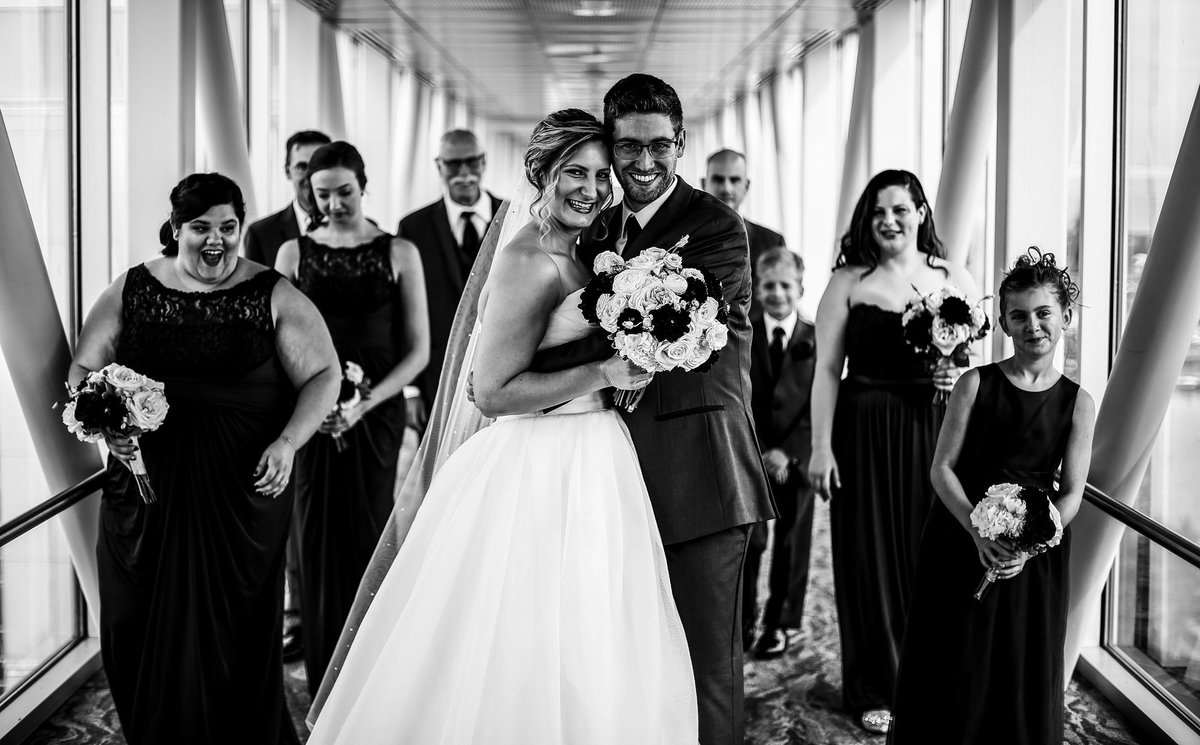 Bride and groom pose with their bridal party on the skybridge at Sheraton Erie Bayfront Hotel