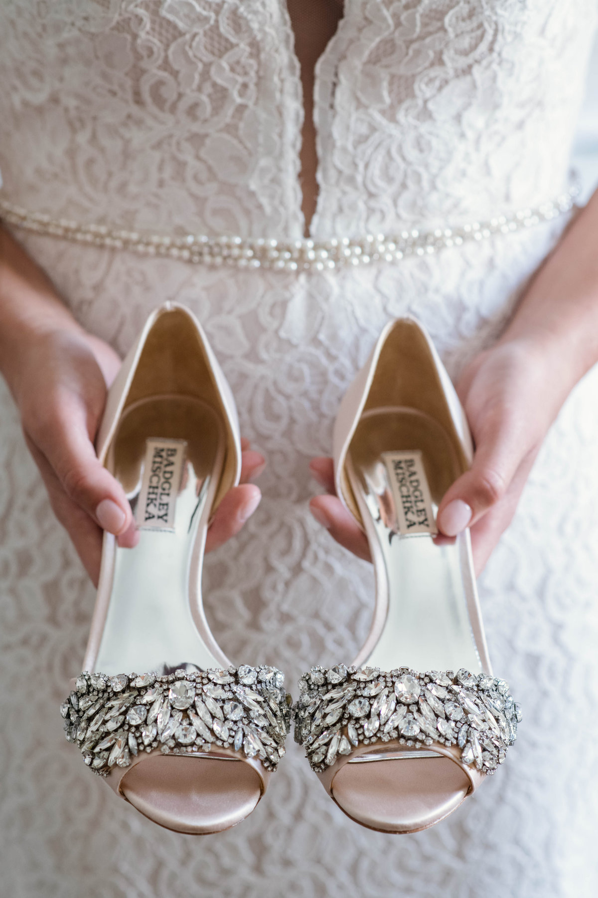 photo of bride holding wedding shoes from wedding at the Mansion at Timber Point