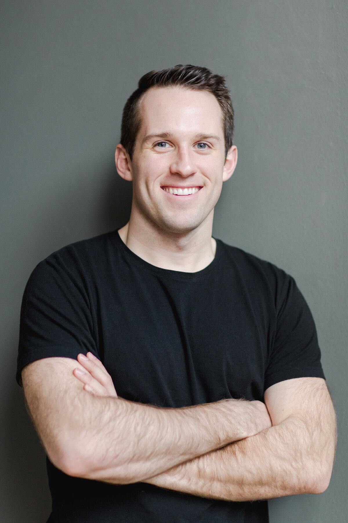 man in black top with his arms folded and leaning up against a wall smiling at the camera