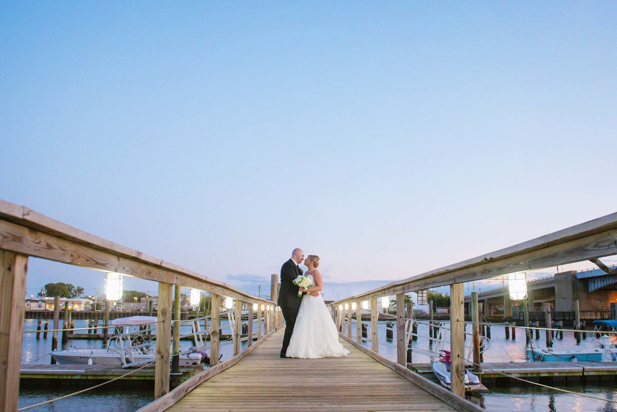 Bride and groom on the dock of Bridgeview Yacht Club
