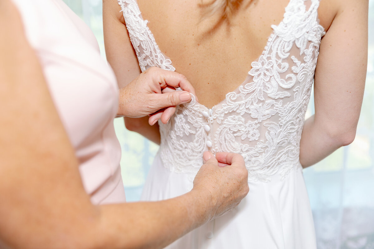 Mom Buttoning Bride's Gown
