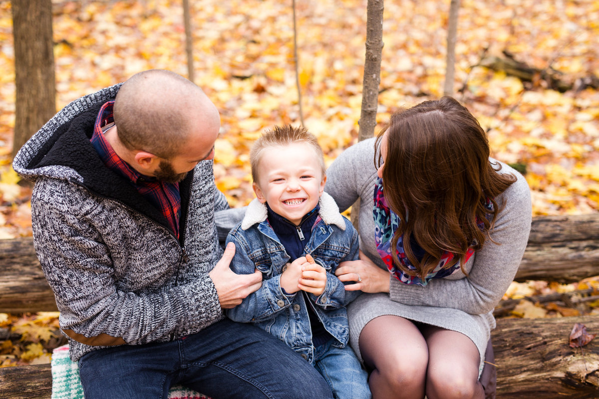 Parents sitting on log and tickling son {Etobicoke Family Photographer}