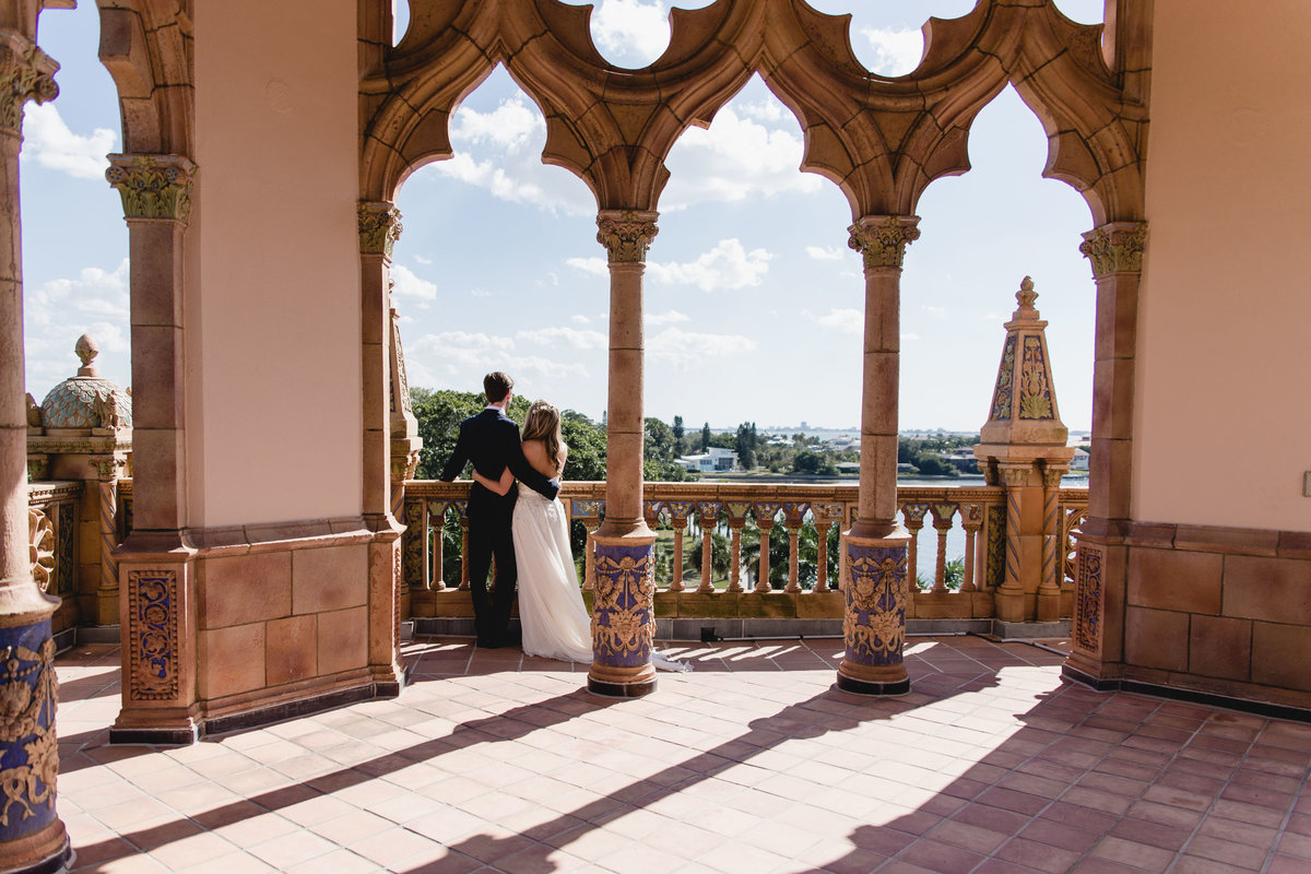 Bride and groom embracing and looking out over balcony