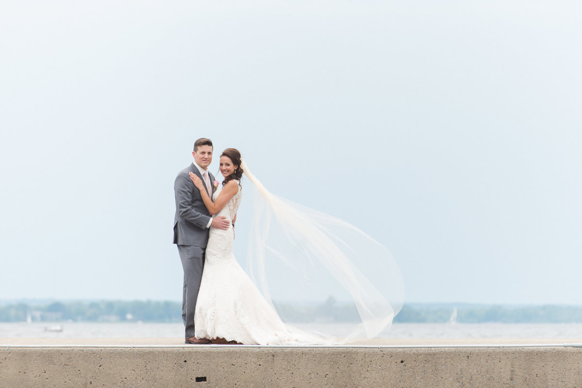 Bride and groom standing on pier with cathedral veil blowing in the wind