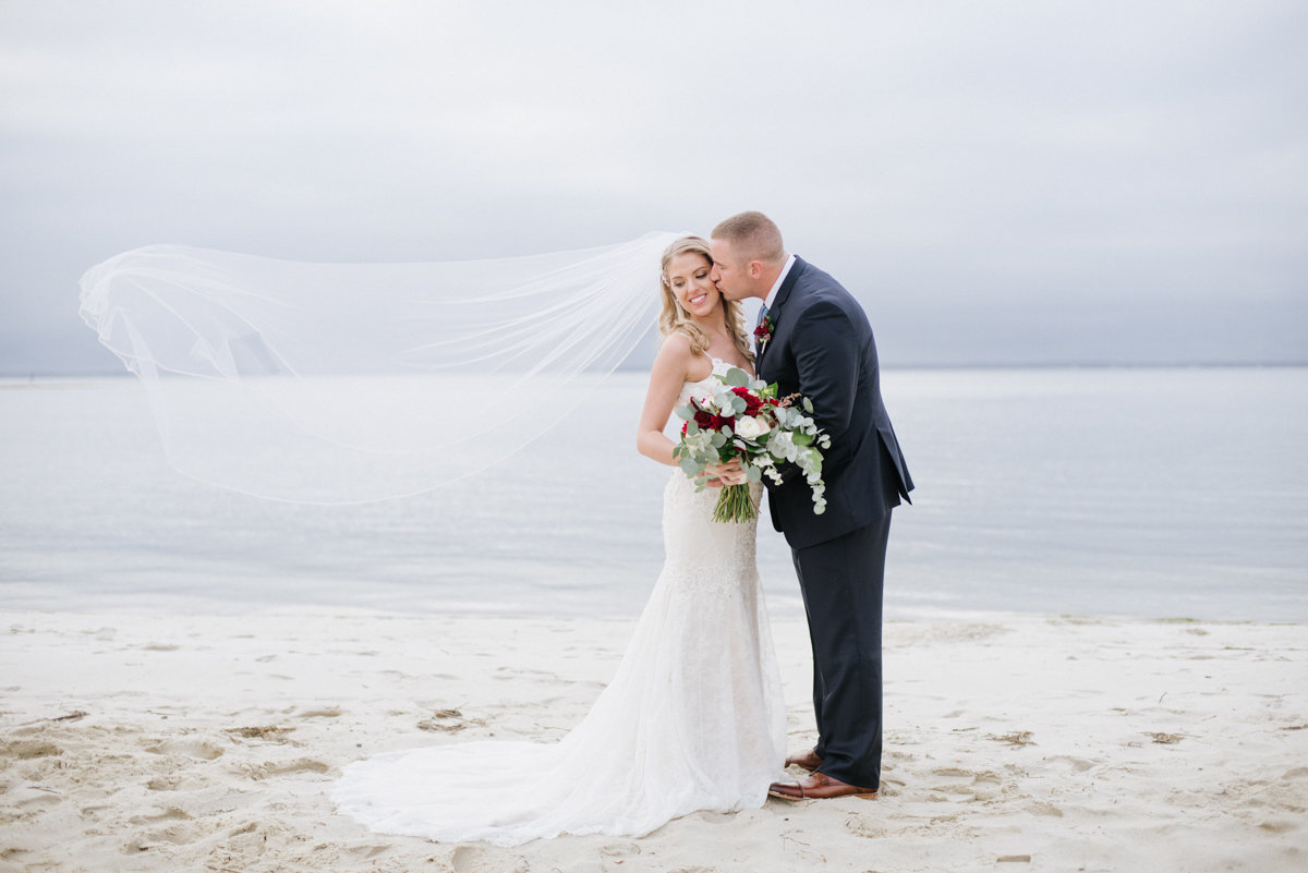 wedding photo on beach with cathedral veil