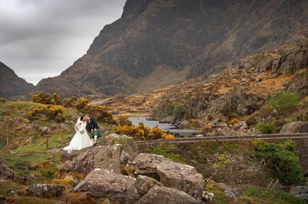 Bride in A-line wedding dress standing on an old stone bridge with her groom wearing a Scottish kilt at the Gap of Dunloe