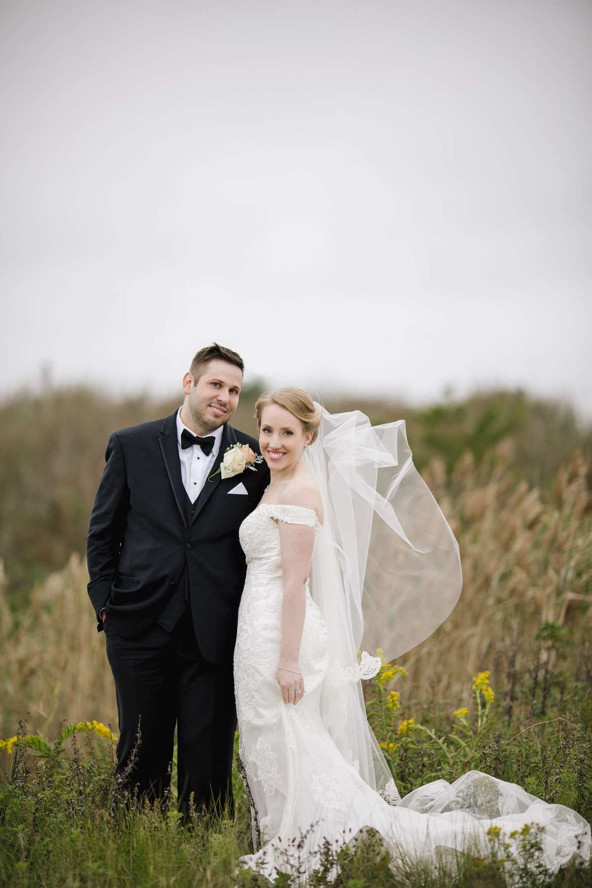 bride and groom in tall grass at  spring lake wedding