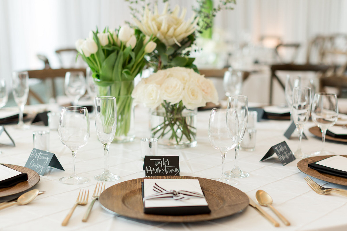 white floral centerpiece, wood charger, gold flatware