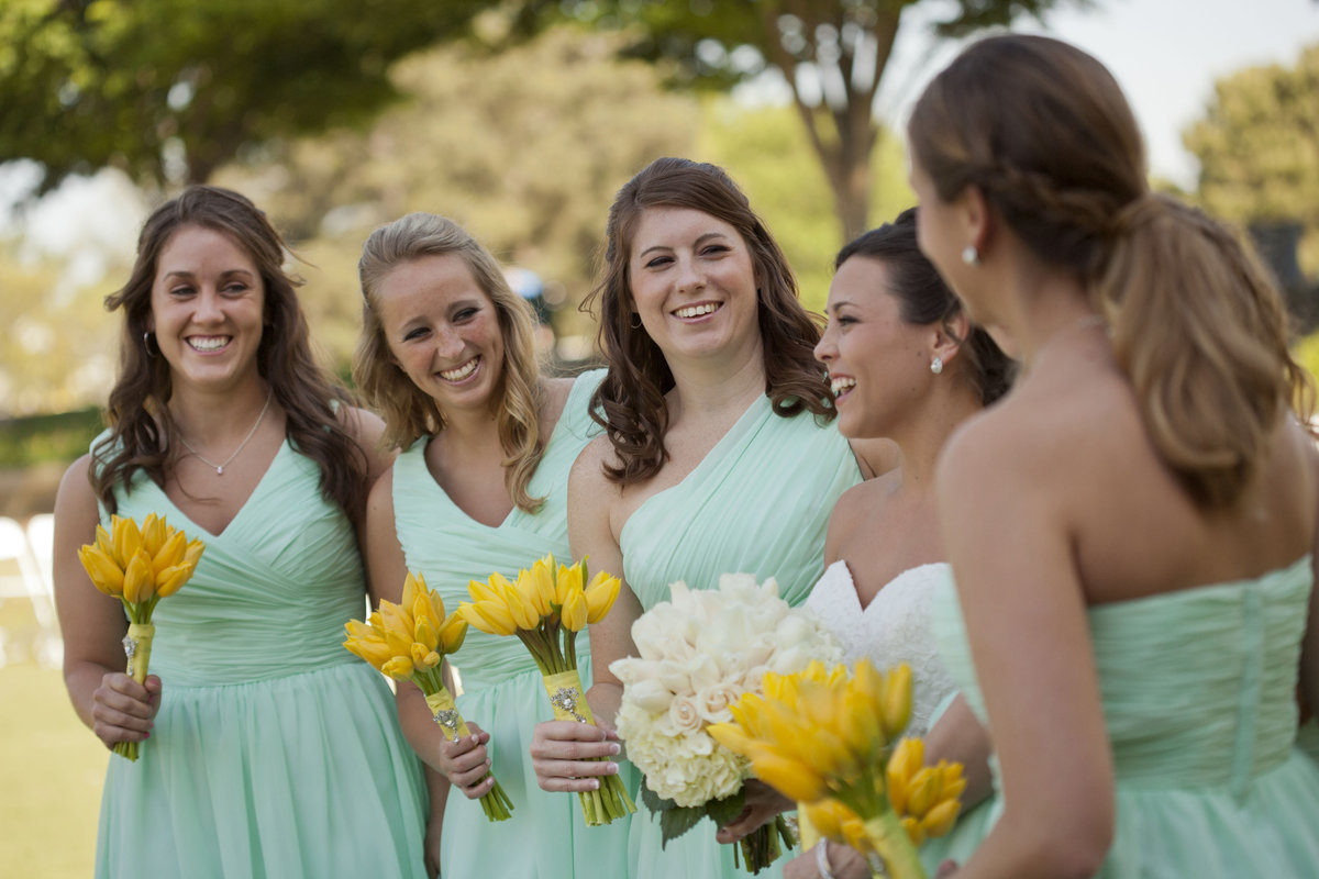 bridesmaids in teal dresses with  yellow tulips