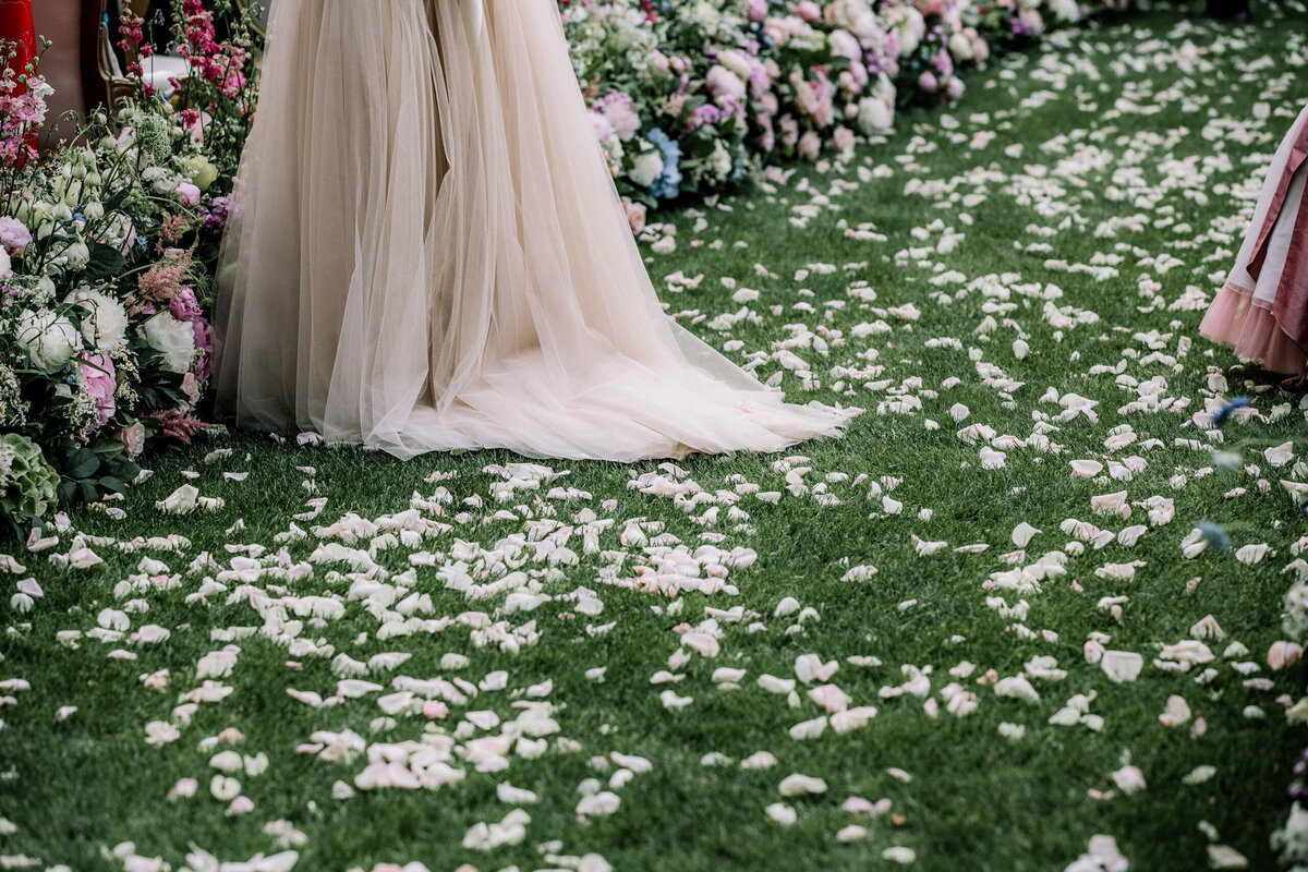 Rose petal confetti lies on the grass aisle lined with colourful flowers, and a luxury wedding dress.