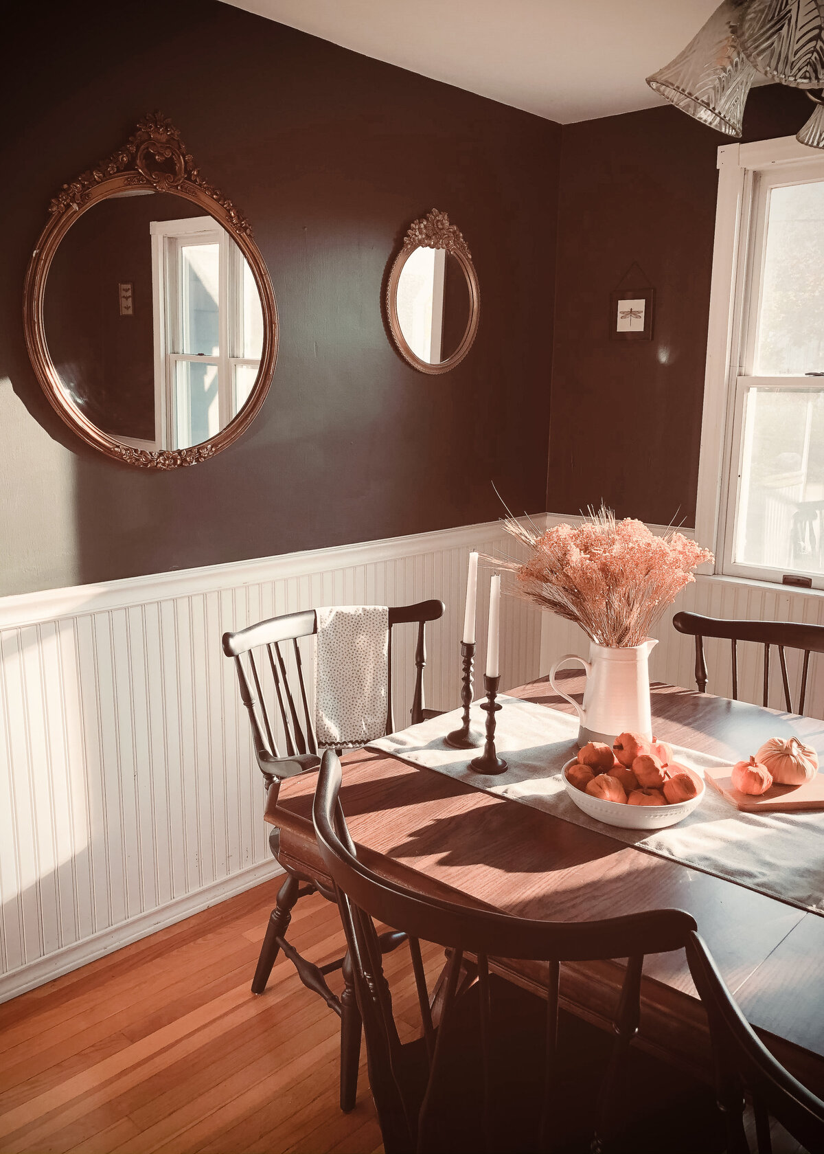 A dining room is styled with two-tone walls in white and black with a dark wood table displaying a ceramic white jug.