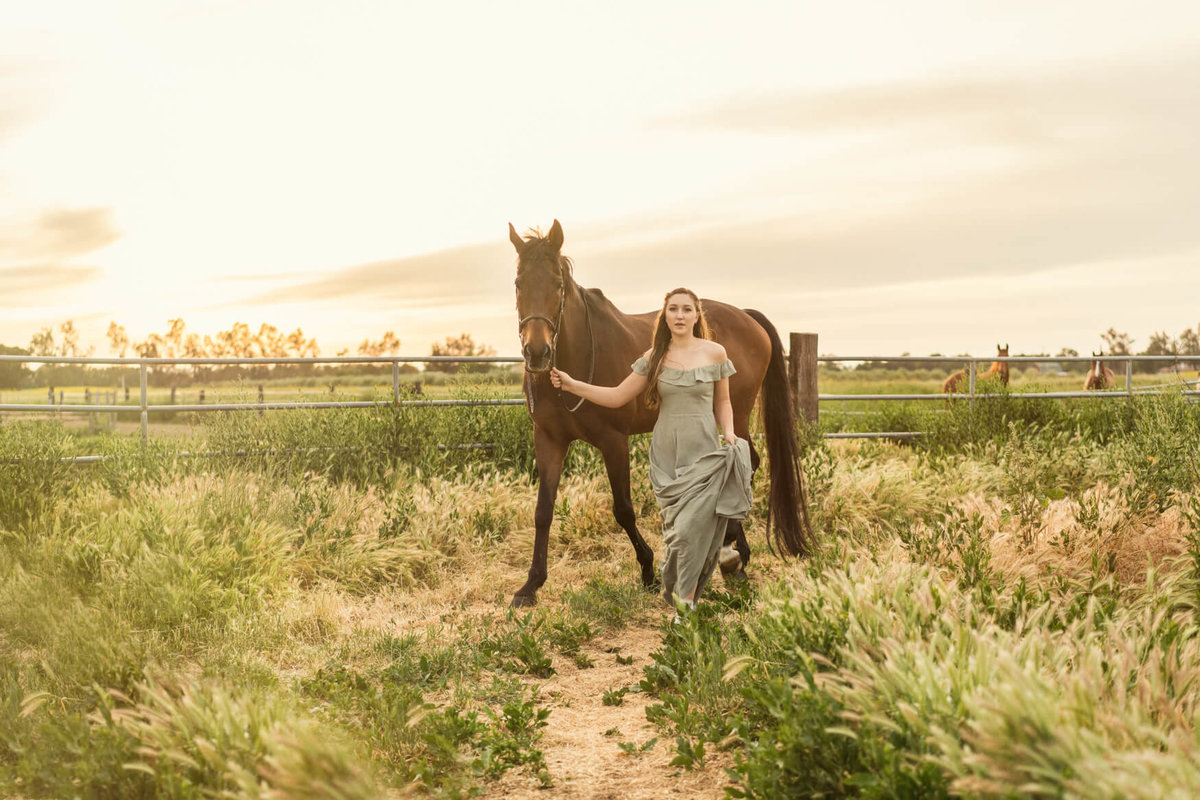 Cassidy walking her horse for her senior photos