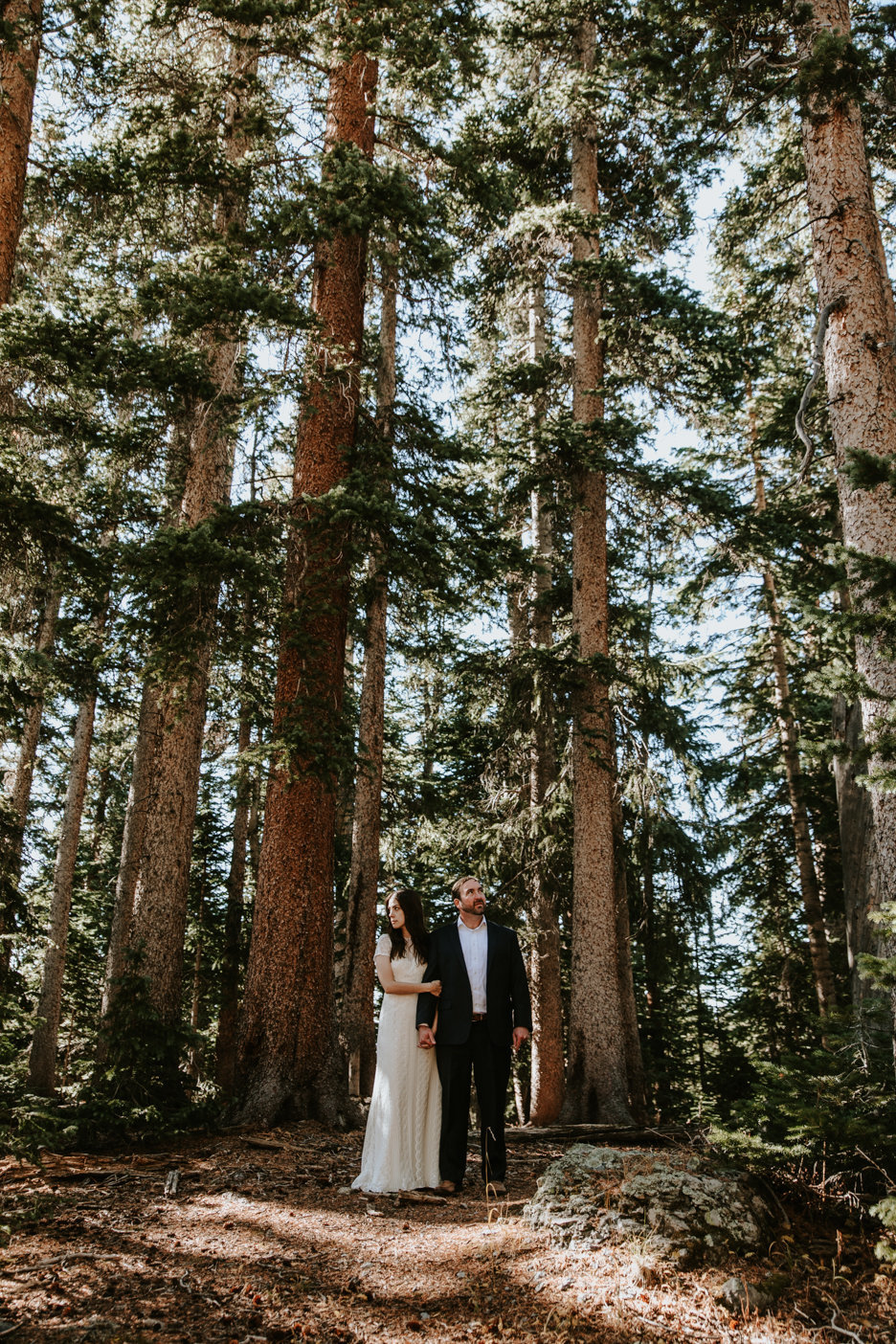 a couple posing under tall trees at the Observatory at Alta Lakes in Telluride, CO