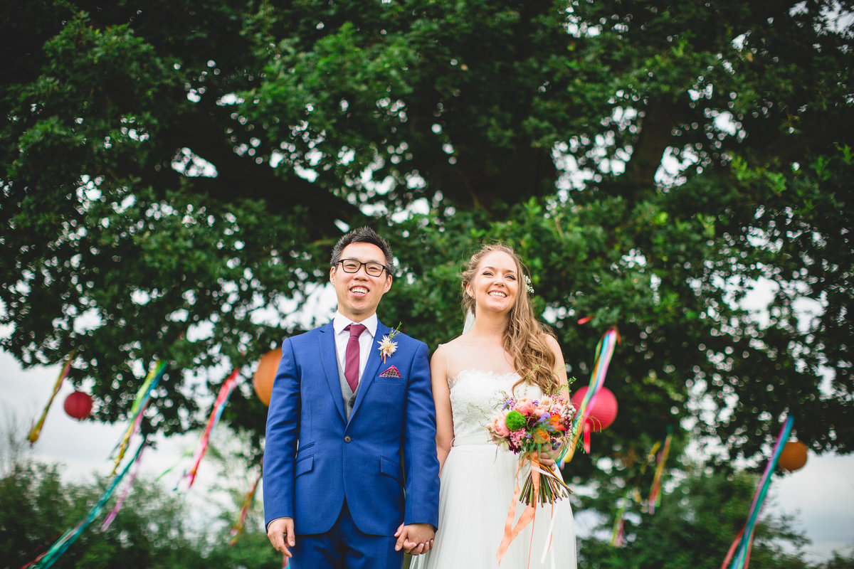 couple with tree and colourful lanterns at this boho wedding