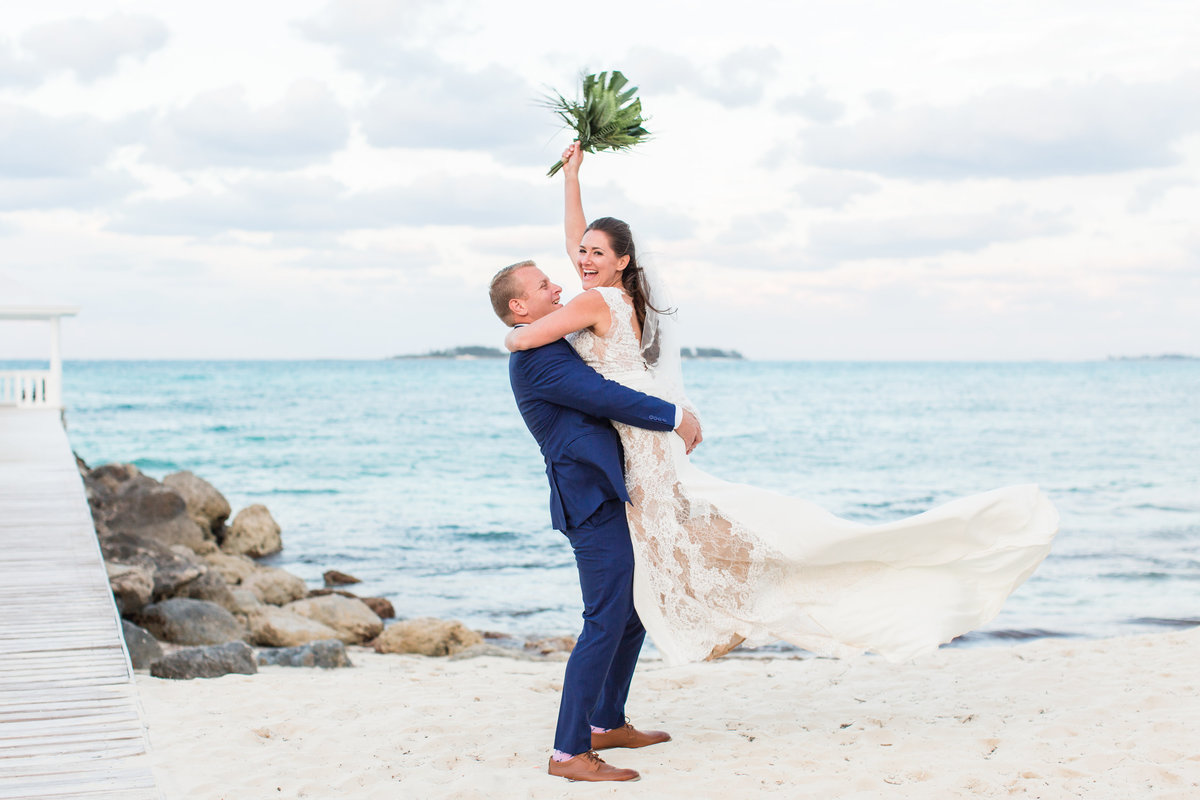 Groom holding bride in the air on the beach in the Bahamas