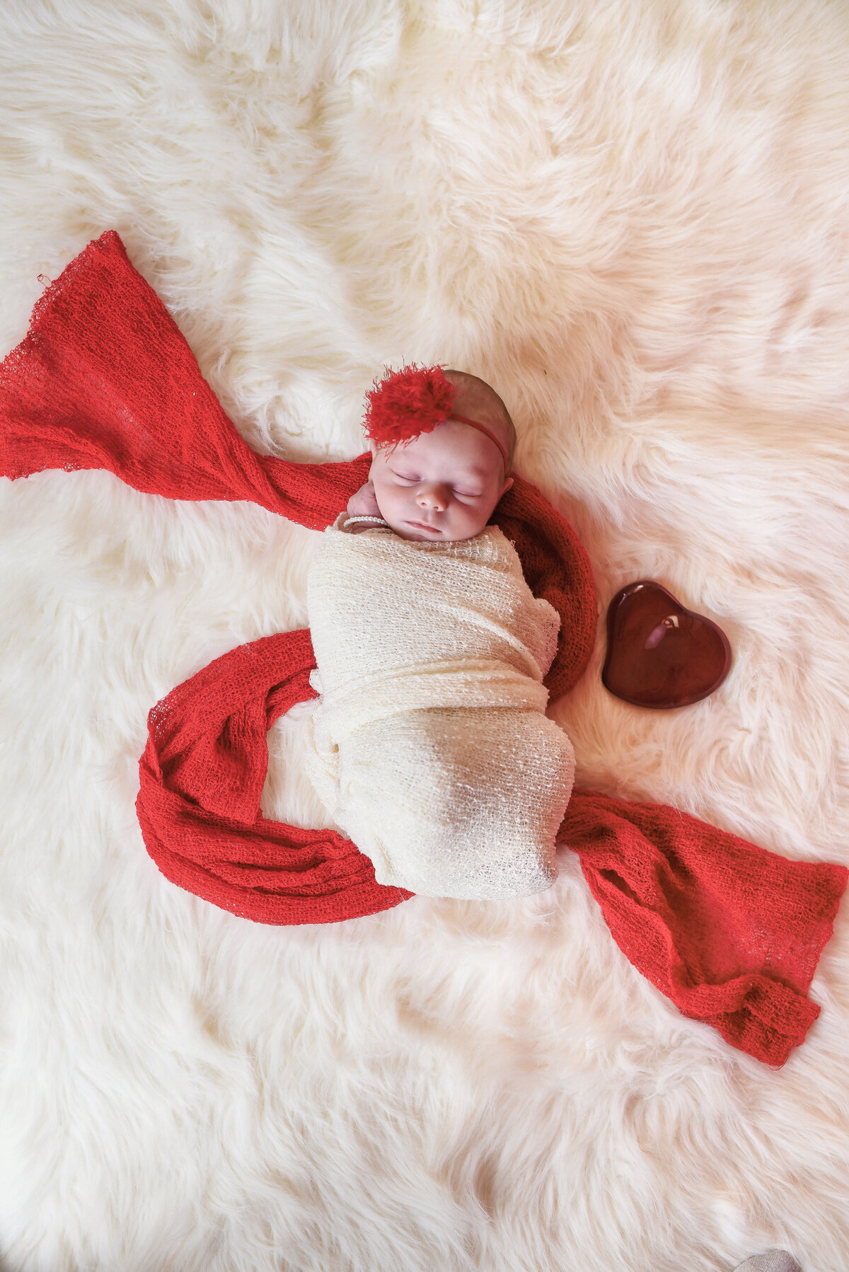 Beautiful Mississippi newborn photography: newborn girl red with a red glass Tiffany heart for Valentines in Mississippi