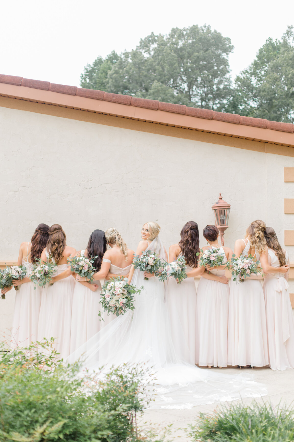 bridesmaids backs with bouquets at running hare vineyard wedding by southern maryland wedding photographer costola photography