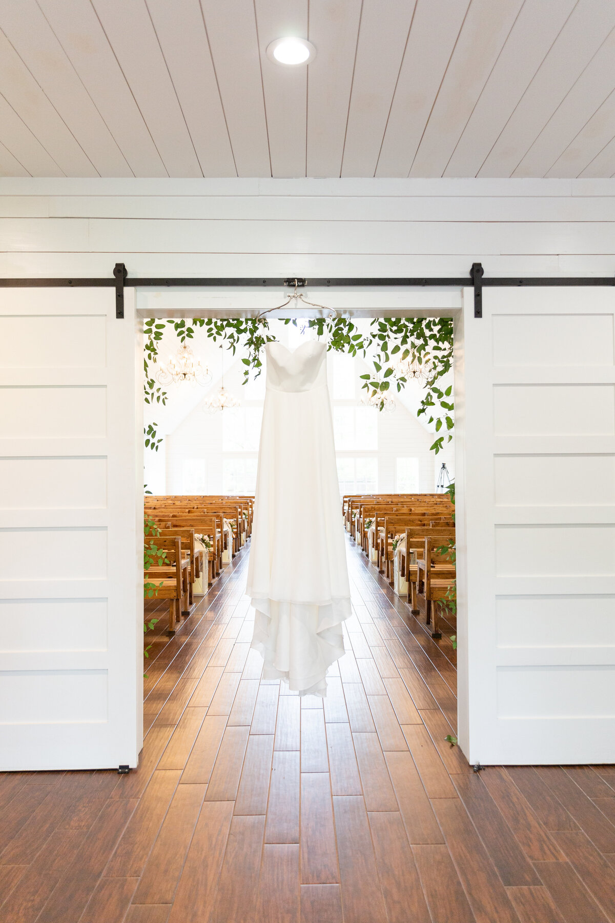 Wedding Dress Hanging in Rustic White Chapel