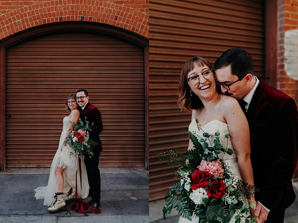 Groom stands behind bride while she holds the bouquet and he kisses her neck