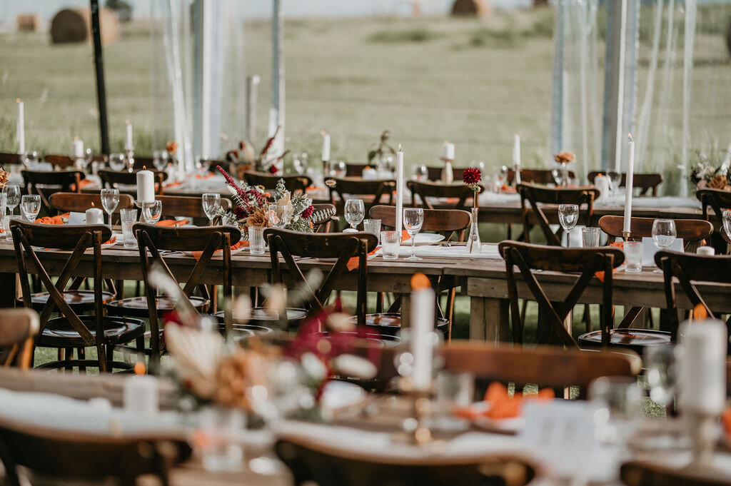 reception wood tables and chairs with white candles and floral arrangements
