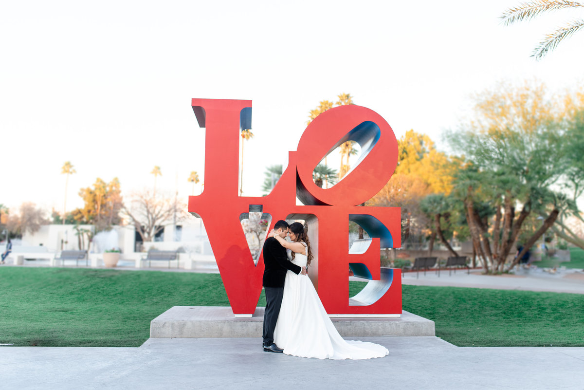 bride and groom hugging in front of LOVE sign in scottsdale arizona
